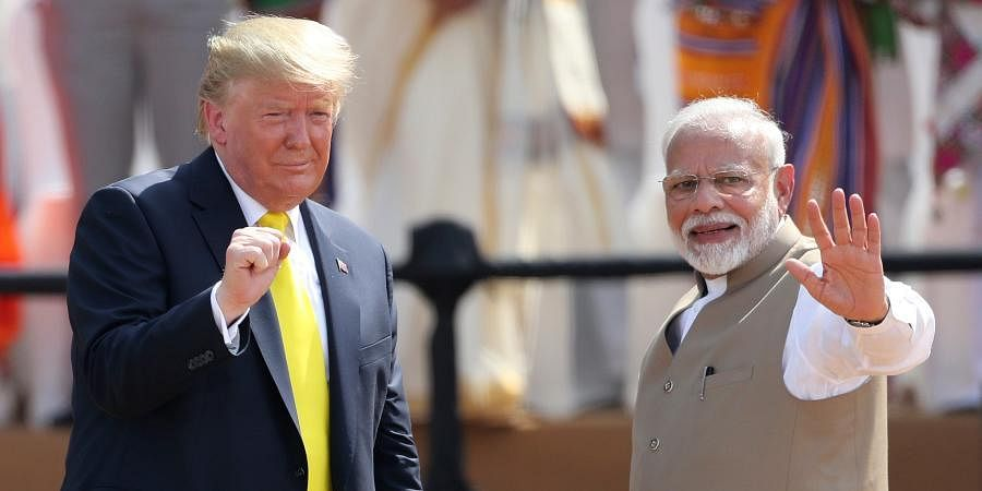 PM Narendra Modi, right, waves as US President Donald Trump reacts to the crowd during the 'Namaste Trump' event at Sardar Patel Stadium in Ahmedabad.