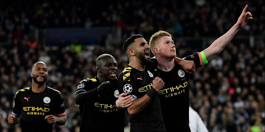 Manchester City's Belgian midfielder Kevin De Bruyne (R) celebrates his goal with teammates during the UEFA Champions League round of 16 first-leg football match between Real Madrid CF and Manchester City at the Santiago Bernabeu stadium in Madrid on February 26, 2020.