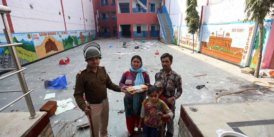 A Delhi Police sub -inspector offers his food to a school guard and his family at Rajdhani Public School at Shiv Vihar in northeast Delhi