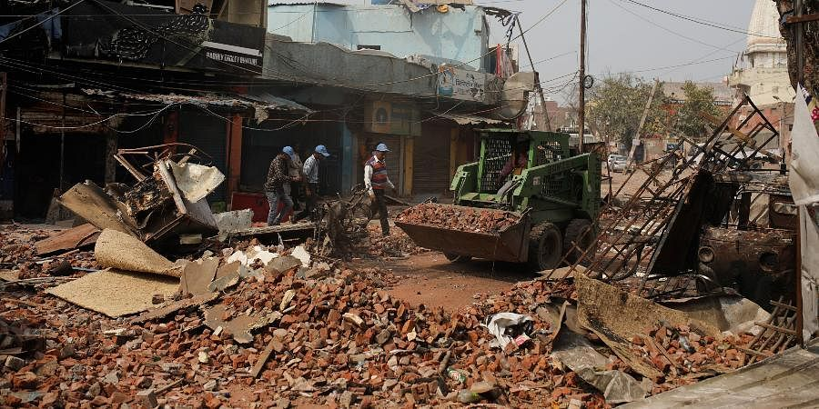 Delhi municipal workers remove bricks and rocks from a street vandalized in Tuesday's violence in New Delhi.
