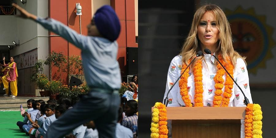 US First Lady Melania Trump, background, cheers as a boy dances impromptu while sitting with other children in the lawn at Sarvodaya Co-Educational Senior Secondary School in New Delhi.