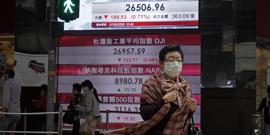 A woman walks past an electronic board showing Hong Kong share index outside a local bank in Hong Kong, Thursday, Feb. 27, 2020. Shares fell in Asia on Thursday after President Donald Trump announced the U.S. was stepping up its efforts to combat the virus outbreak that began in China.