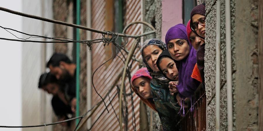 Muslim women look out of a window as security officers patrol a street in New Delhi.