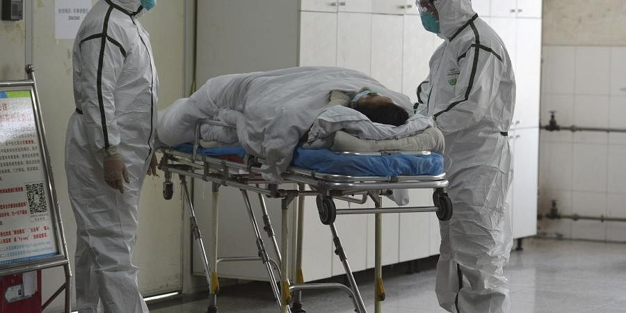 Medical workers in protective suits move a coronavirus patient into an isolation ward at the Second People's Hospital in Fuyang in central China's Anhui Province, Saturday, Feb. 1, 2020. (Photo | AP)