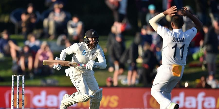 New Zealand's Tom Blundell (L) runs as India's Mohammed Shami (R) reacts on day one of the second Test cricket match.