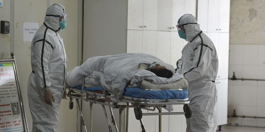 Medical workers in protective suits move a coronavirus patient into an isolation ward at the Second People's Hospital in Fuyang in central China's Anhui Province, Saturday, Feb. 1, 2020. (Photo   AP)