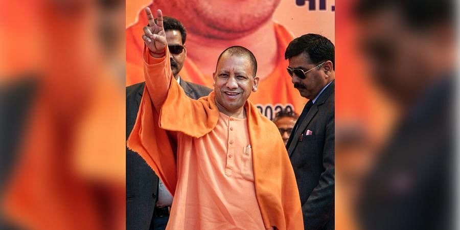 Uttar Pradesh Chief Minister Yogi Adityanath displays victory sign during an election campaign rally for the upcoming Delhi Assembly polls at Uttam Nagar in New Delhi Monday