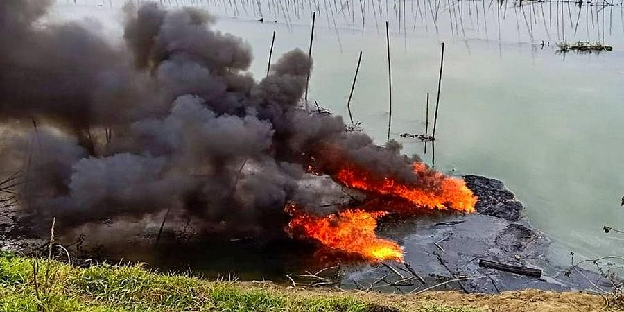 Plumes of smoke rise over a small stream of the Burhi Dihing River after a crude oil pipeline exploded in the area at Naharkatia town of Dibrugarh district Monday Feb. 3 2020.