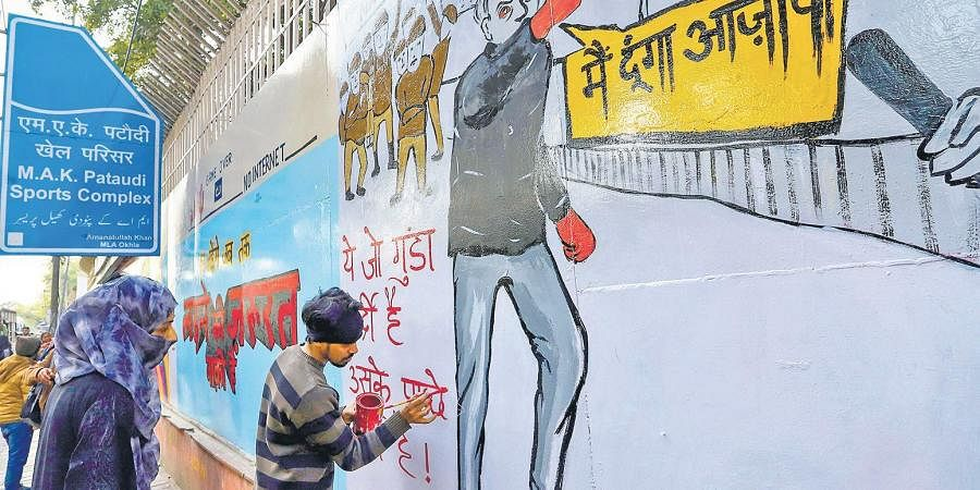 An activist paints graffiti on a wall to protest against the recent incidents of firing at Jamia Millia Islamia & Shaheen Bagh