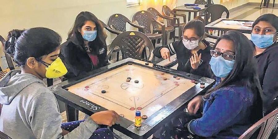 Indian nationals who were airlifted from coronavirus-hit Hubei, China, play carrom inside a quarantine facility set by up ITBP at Chhawla, New Delhi