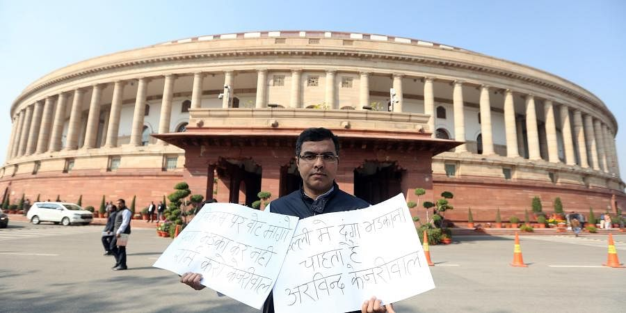 BJP MP Parvesh Verma displays a placard written 'shooter of Shaheen Bagh is AAP worker' at Parliament