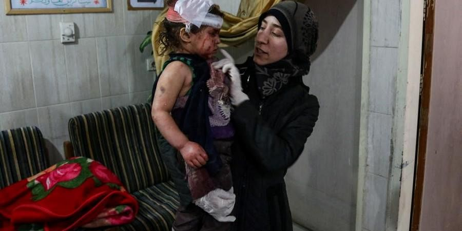 Syrian paediatrician doctor Amani Ballour holds a wounded child in her arms at the Cave hospital in Kafar Batna, Syria, on February 6, 2018.