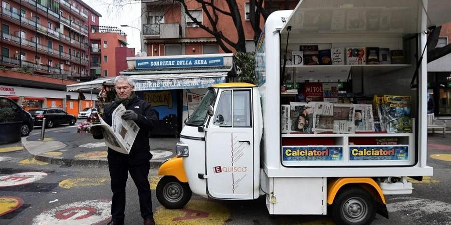 Andrea Carbini stands by his three-wheeled transporter newsstand parked next to a closed media store during his daily itinerary in different points of Milan on January 25, 2020.
