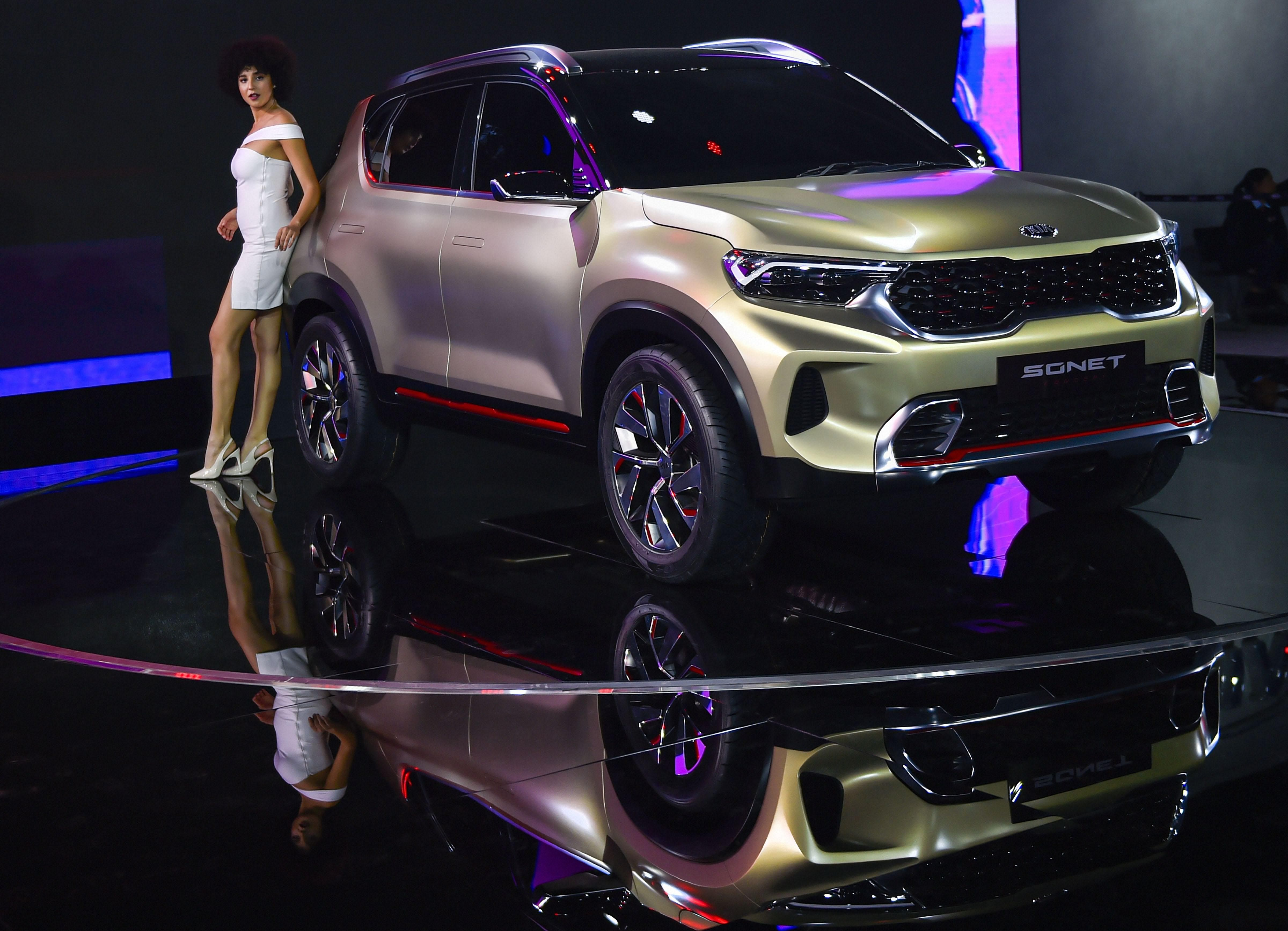 A model poses next to a Kia Sonnet car displayed at the Auto Expo 2020 in Greater Noida