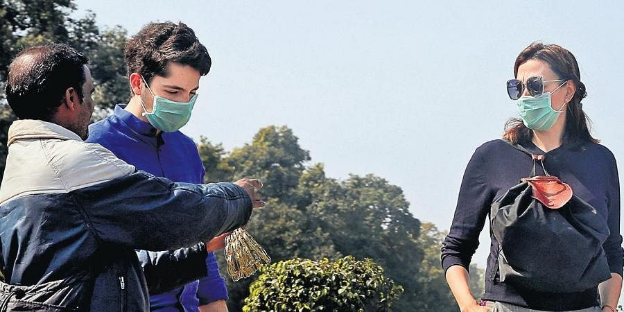 Tourists wear medical-masks as a precautionary measure against novel coronavirus in New Delhi.