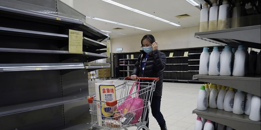 A woman wearing face mask, walks past empty shelf of tissue papers at a supermarket in Hong Kong, Friday, Feb. 7, 2020.