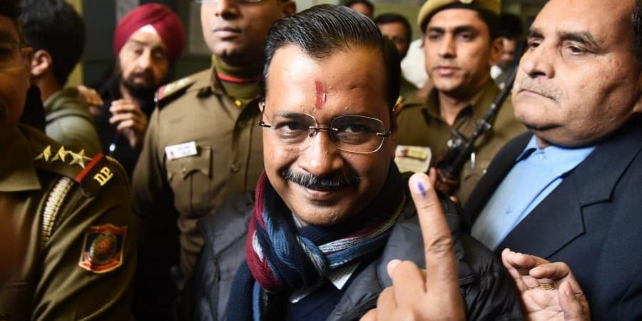 Delhi Chief Minister Arvind Kejriwal shows their ink-marked fingers after voting at a polling station in New Delhi on Saturday. (Photo | Parveen Negi/EPS)