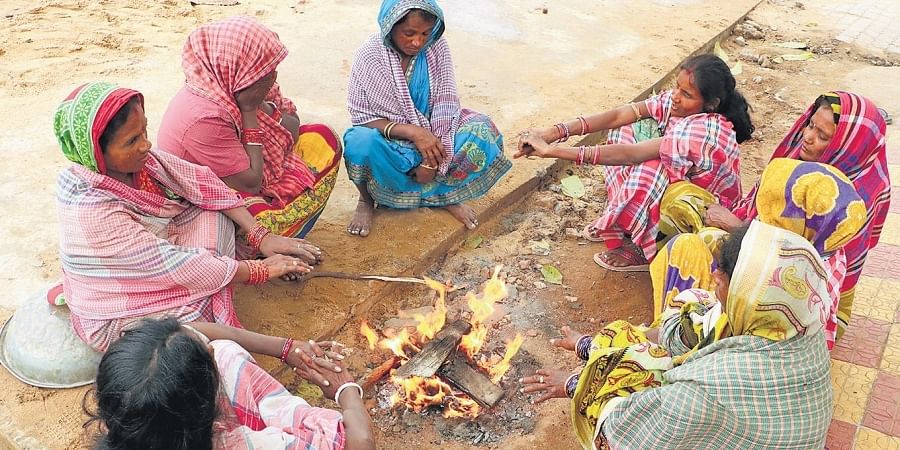 Women gather near a bonfire to keep themselves warm on a cold Friday in Bhubaneswar.