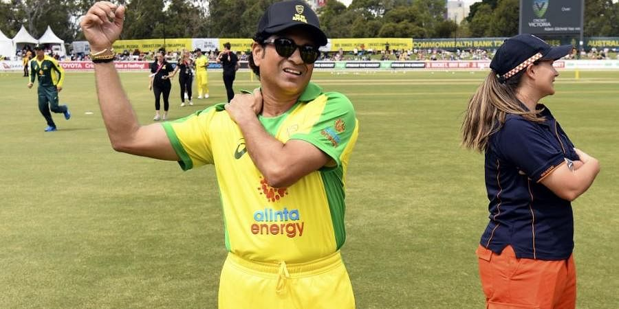 Former Indian cricket player Sachin Tendulkar (L) stretches before a celebrity cricket match to raise funds for those affected by the Australian bushfires. (Photo   AFP)