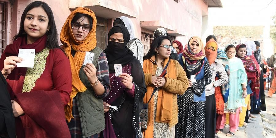 Muslim women show the election cards as they stand in queue to cast their votes at a polling station near the protest site for the protest against the Citizenship Amendment Act CAA and National Register of Citizens NRC in Shaheen Bagh area during Delhi State Assembly elections in New Delhi 08 February 2020.