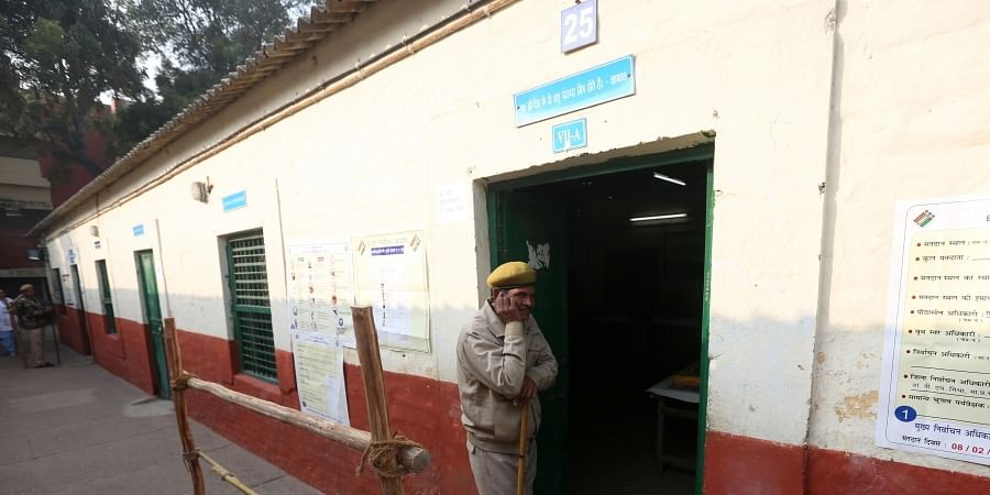 Police personnel stand guard at a voting center during the Delhi Assembly elections in New Delhi on Saturday.