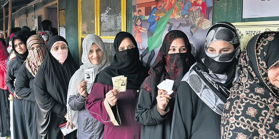 Women show their election cards as they stand in queue to cast their votes at a polling station near the anti-CAA protest site  in Shaheen Bagh.