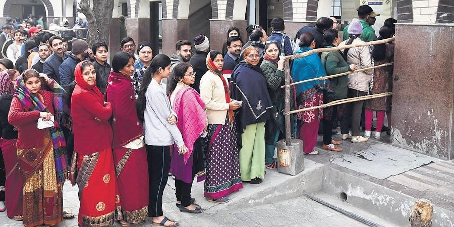 People check their name in a voter list outside a polling station during the during the Delhi Assembly elections at Satbadi area in New Delhi on Saturday.