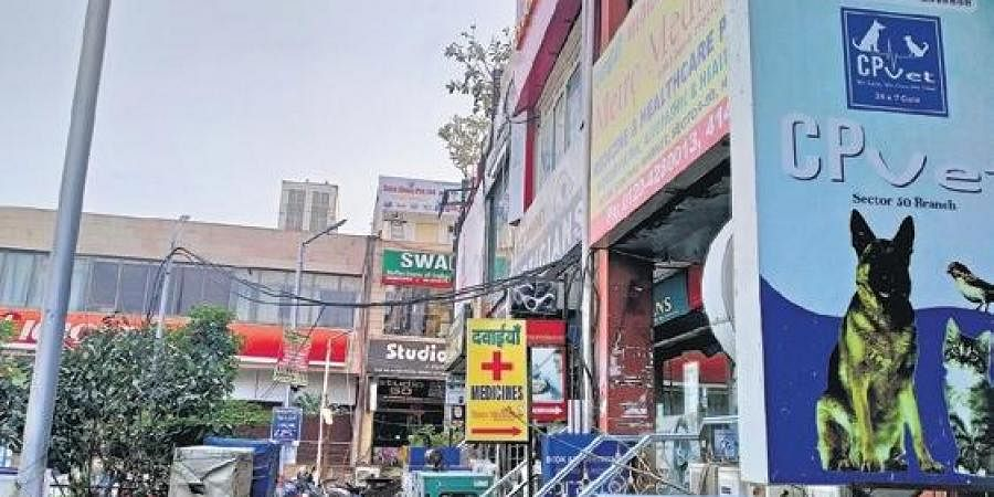 (Inset) Noida's Sec-50's favourite chaat-walla put up a board informing locals about change in venue; views from the block market