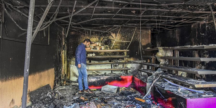A man stands in a burnt shop which was set ablaze by rioters in a violence-affected area of Northeast Delhi. (Photo | PTI)