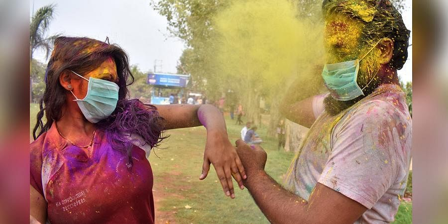 People wearing masks throw colour at each other during Holi at Necklace Road