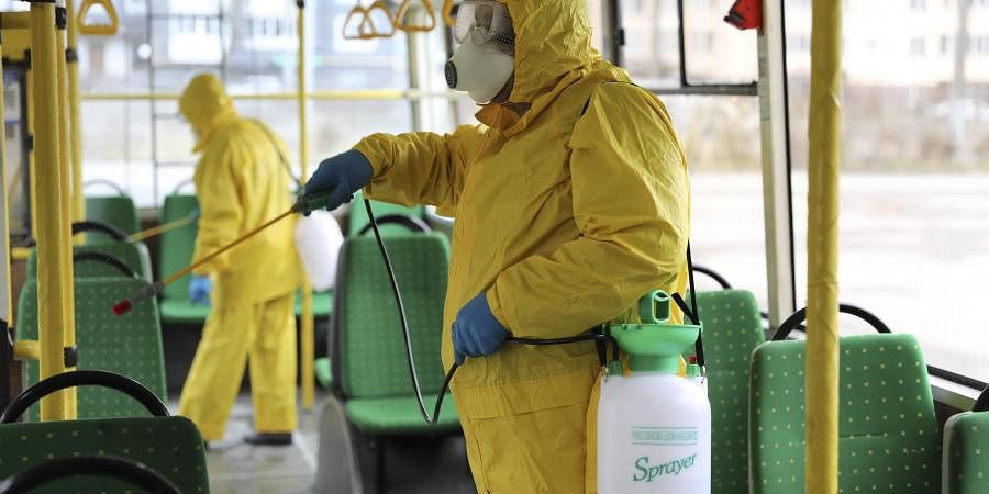 Employees wearing protective gear spray disinfectant to sanitize a passenger bus as a preventive measure against the coronavirus. (Photo | AP)