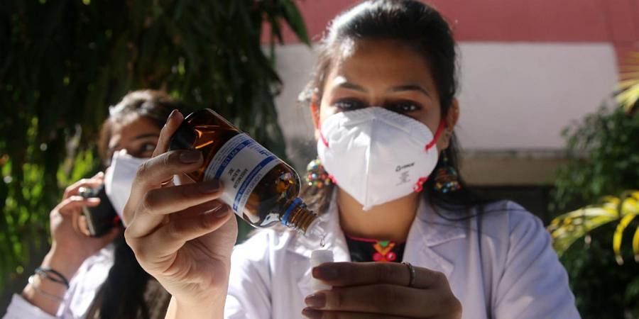 A doctor pours medicine to be used as a precaution against COVID-19, at Nehru Homeopathic Medical College