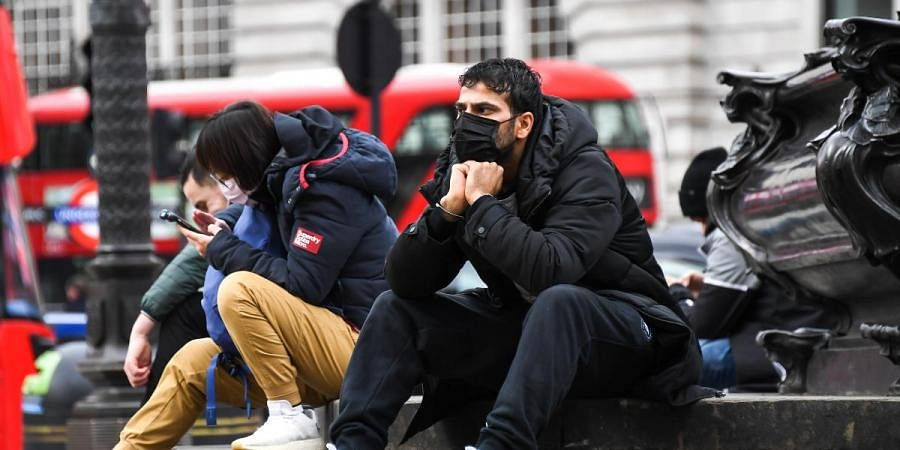 People wear face masks as they sit on the Shaftesbury Memorial Fountain in Piccadilly Circus, in London, Friday, March 13, 2020.