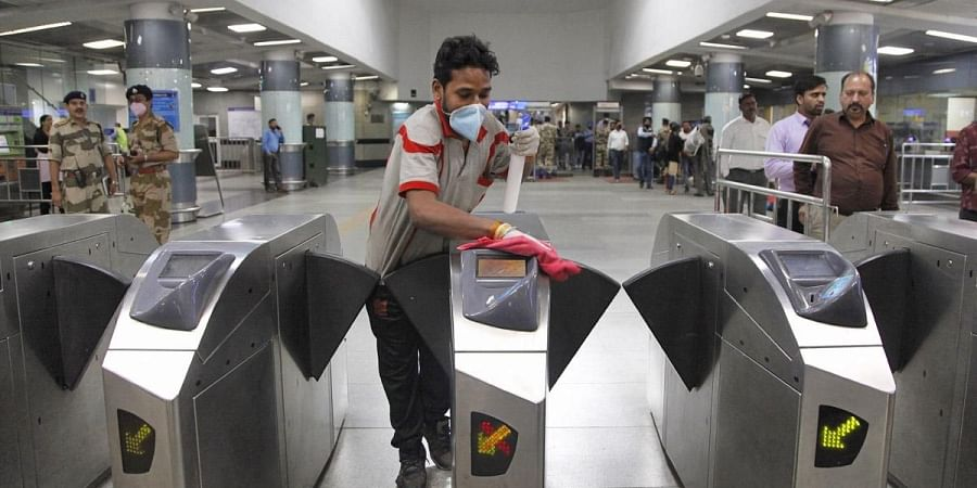 A cleaning staff disinfects the entry gates at the Rajiv Chowk Metro station in Delhi, Coronavirus
