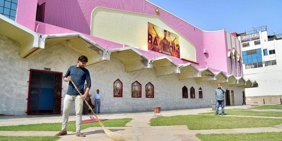 A worker sweeps the lawn of a closed cinema hall in view of the novel coronavirus outbreak in Bikaner