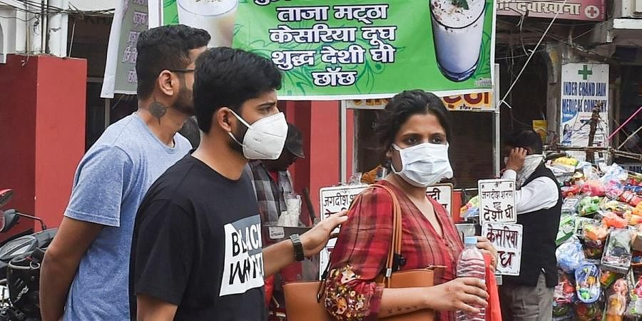 People wear protective masks in view of coronavirus pandemic at a market in Lucknow