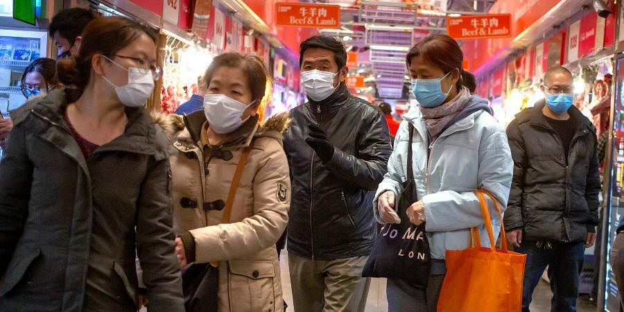People wear face masks as they shop at a market in Beijing.
