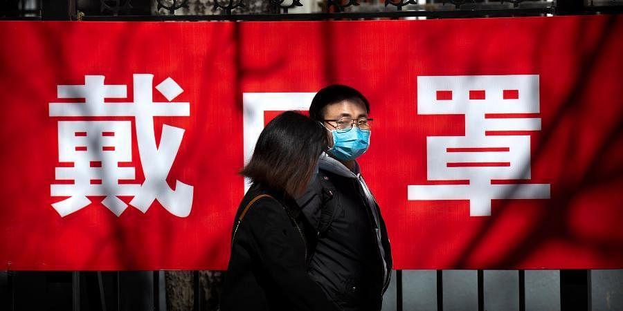 People walk past a propaganda banner reading wear a face mask in Beijing.