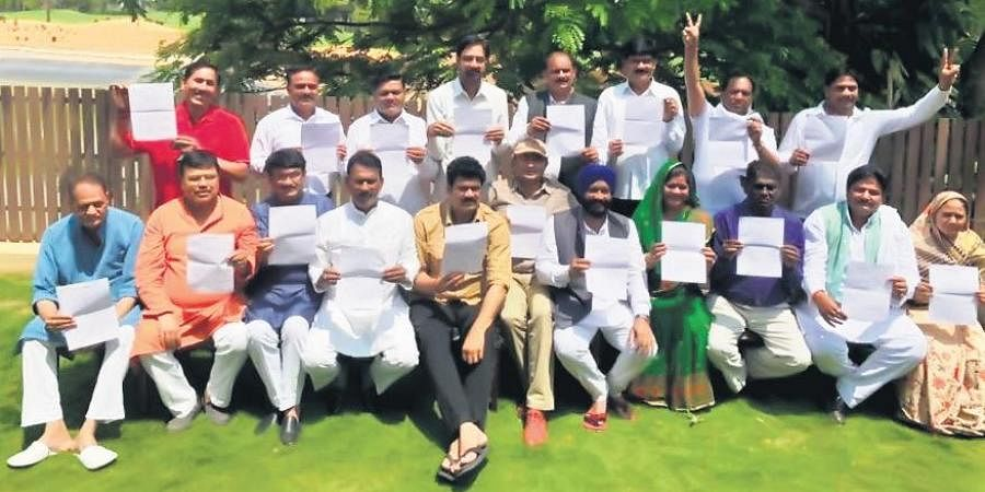 The 19 Madhya Pradesh rebel Congress MLAs pose with their resignation letters in Bengaluru on Tuesday.