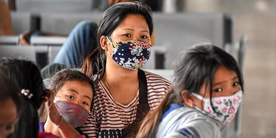 Passengers wear masks as a preventive measure against coronavirus at Guwahati Railway Station on Monday