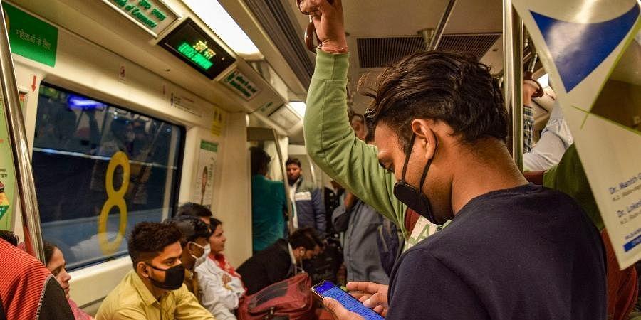 Passengers wear masks while travelling in a Delhi metro train as a prevention measure against coronavirus