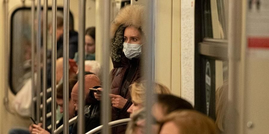 A woman wears a medical mask holds a smartphone standing inside a metro train in Moscow on Monday