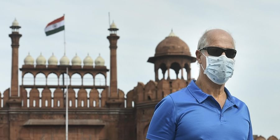 A visitor wears a mask to mitigate the spread of coronavirus, at Red Fort in New Delhi