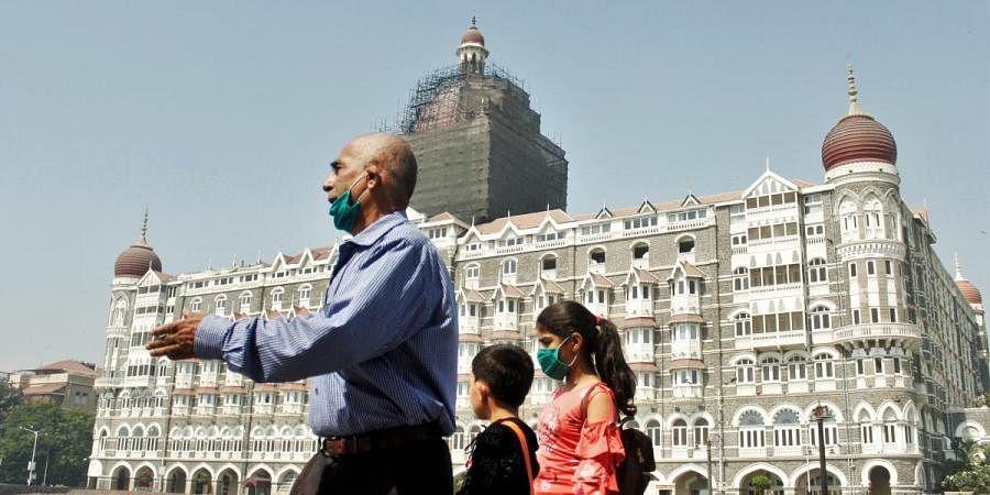 People wearing masks as a precautionary measure in the wake of coronavirus as they walk outside The Taj Mahal Palace Hotel, in Mumbai on Tuesday