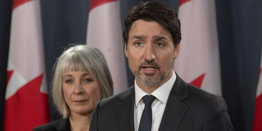 Canada PM Justin Trudeau speaks during a news conference in Ottawa as Minister of Health Patty Hajdu looks on