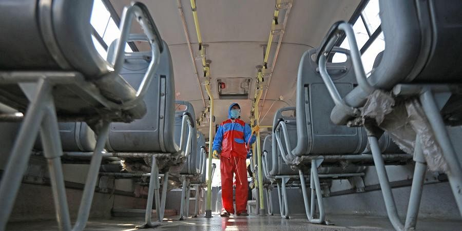 A volunteer sprays disinfectants in a DTC bus in the wake of coronavirus at Sunehri Pul bus depot,in New Delhi