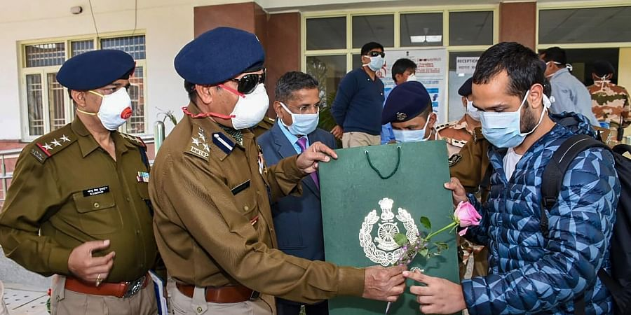 ITBP officers present a rose to a Wuhan-return Indian as he is released from the ITBP quarantine facility at Chhawla New Delhi Monday Feb. 17 2020. (Photo | PTI)
