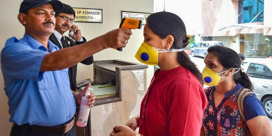 An official uses thermal screening device on visitorsin the wake of coronavirus pandemic. (Photo | PTI)