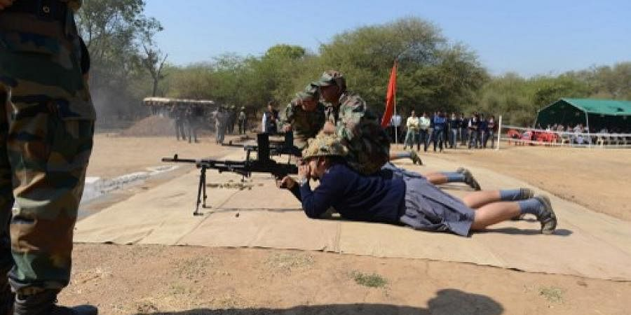 Indian Army soldiers help schoolchildren to fire a Light Machine Gun (LMG) during a demonstration on the eve of Indian Republic Day at the Golden Katar Division Parbat Ali Brigade Campus on the outskirts of Gandhinagar.
