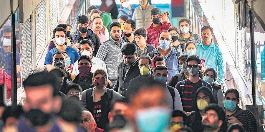 Passengers wear masks as a precautionary measure against the Coronavirus pandemic at a railway station in Jammu.